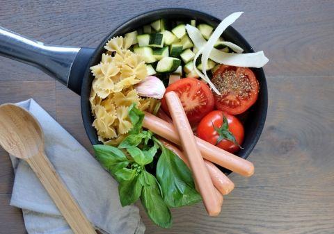 Pelez et hachez l'oignon et l'ail, faites-les revenir 3 minutes avec l'huile dans une casserole. Ajoutez l'eau, les pâtes, les saucisses Knacki coupées en grosses rondelles, l'origan, les tomates et la courgette coupées en dés, le concentré, salez et poivrez. Laissez cuire 15 minutes à couvert et à feu doux en mélangeant de temps en temps. En fin de cuisson ajoutez le parmesan râpé et le basilic ciselé. Servez sans attendre.