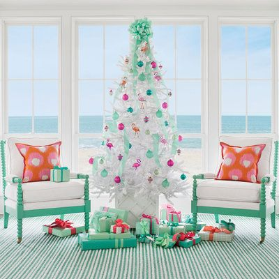 The Frosty Flamingo Tree ~  This groovy palette of sea foam, pinks, and corals is full of retro-inspired fun. The white branches of flocked spruce trees like this one make ornaments in hot hues shine. Conceal the stand in a garden planter—we used a patterned, Chippendale-style container. Channel retro cheer with quirky 1940's saucer ornaments, and then balance the kitsch with translucent jade globes. Crown with a large bow. Let the party begin!