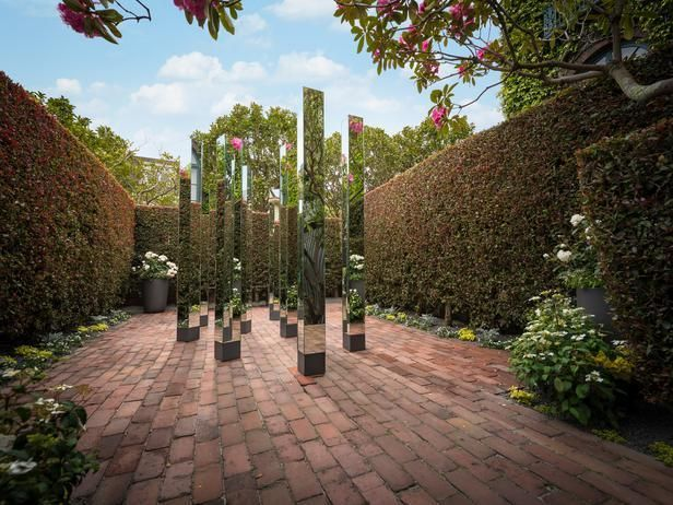 The garden at the San Francisco Decorator Showcase 2014 leads to a final vignette, designed by Kate Webster and Thayer Hopkins to inspire and encourage reflection. A brick path draws the eye toward the abstract, mirrored sculpture that reflects light and shadow.