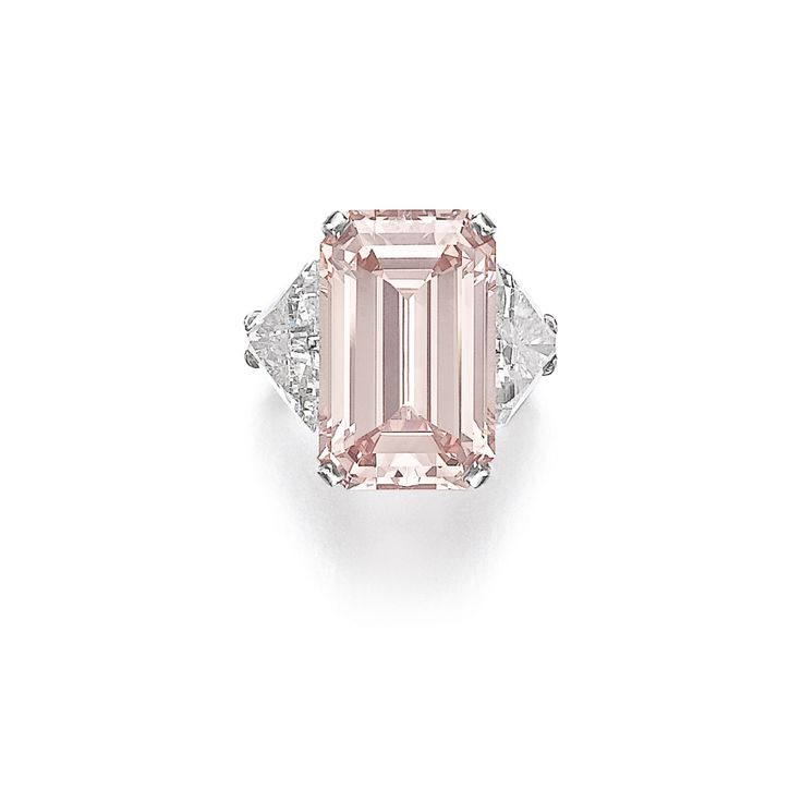 Magnificent fancy intense pink diamond ring Set with a step-cut fancy intense pink diamond weighing 17.07 carats, between triangular diamonds weighing 3.07 and 3.13 carats respectively, size 51.