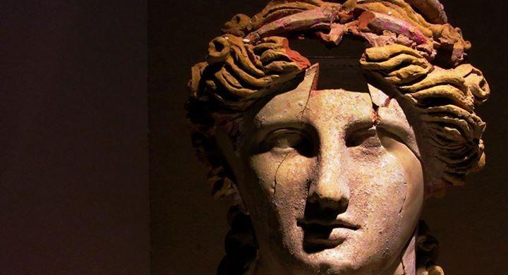 Testa di statua o busto femminile fittile, ricostruita da frammenti. La policromia perfettamente conservata esalta il biondo dei capelli raccolti sopra la fronte da una fascia rossa, mentre il volto appare pallido nell'ingubbiatura bianca. Prodotto esemplare dell'artigianato siracusano di epoca ellenistica. Probabilmente la figura rappresenta Kore