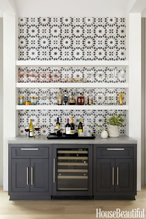 Opt for graphic tiles: Cement tiles from Ann Sacks, installed behind the Thermador gas cooktop and the dry bar beside the dining table, add the right amount of focal-point pattern. Click through for more amazing photos of this farmhouse kitchen.