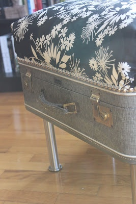 This woman used a pillow, fabric hemmed with stitch witchery (no sewing!), 4stool legs from Ikea, and trim-style tac nails. The lid still opens for storage!