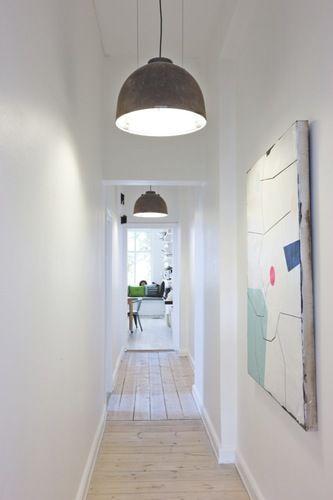 Long couloir blanc rythmé par les suspensions grises et les tableaux au mur. Plancher pin #white #hallway