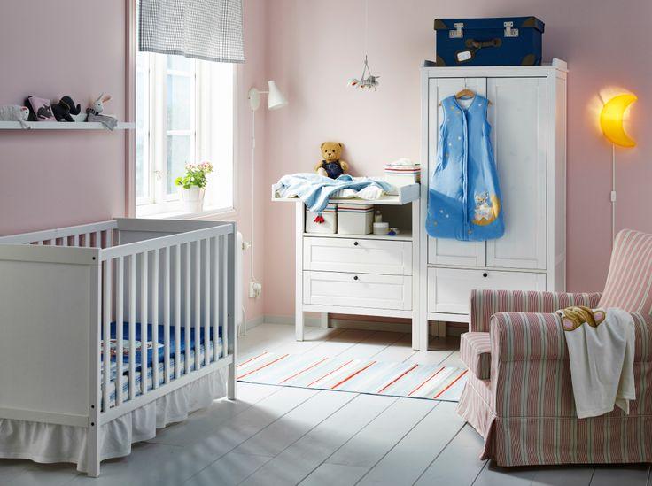 Una habitación de bebé con una cuna, un cambiador y un armario, todo en blanco, y un sillón en rojo/beis.