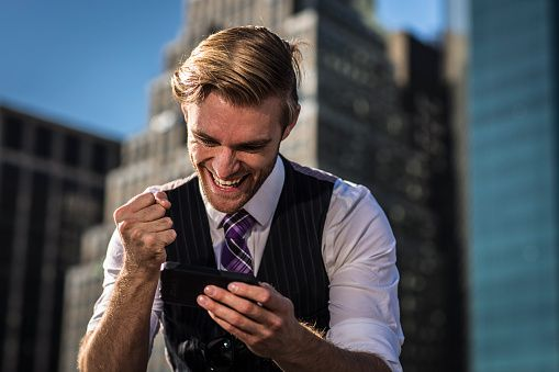 Young businessman in front of office clenching fist at smartphone, New York, USA