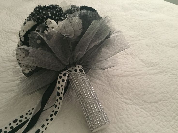 Beautiful B&W flowers of polka dot and check fabrics with button centers form this retro style bouquet.  The handle is fully blinged out and the bouquet finished off with some long matching ribbons. All bouquets can be reproduced in the size and colour of your choice. Feel free to mix and match ideas to make your bouquet more individual. Corsage, MOB and Lapel pins are also available to match your colours. Contact leeann@bejewelledbridal.com.au for more information.
