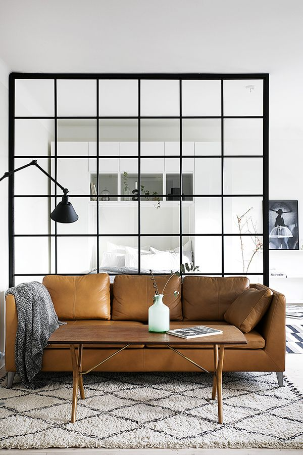 Internal glass doors with black frames and a tan leather sofa