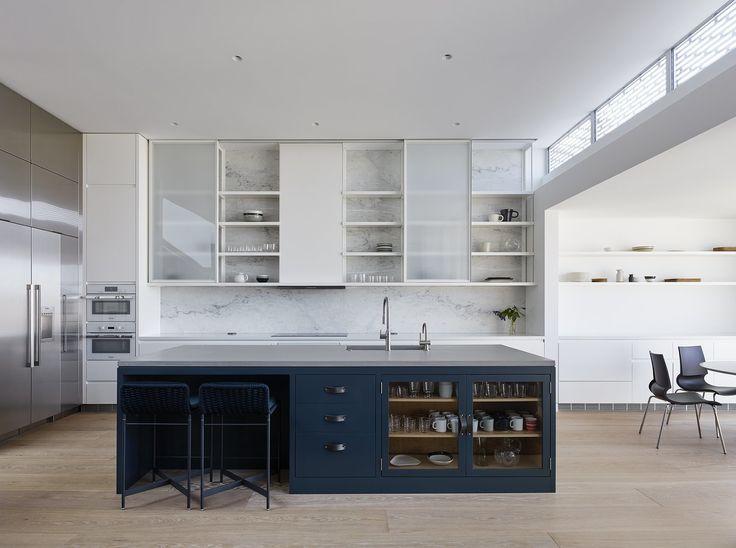 dark kitchen island in white kitchen, marble kitchen wall forms backsplash