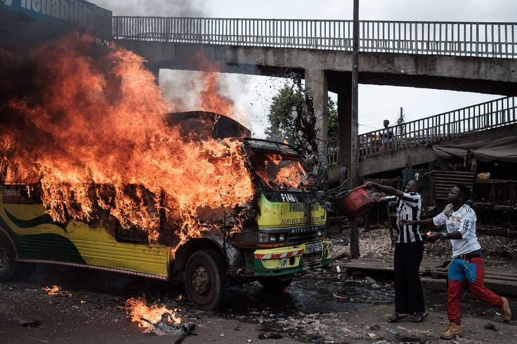 Supporters of Kenyan's opposition party National Super Alliance (NASA) throw water on a burning bus during a demonstration on November 17, 2017, in Nairobi. Three men were shot dead as opposition leader Raila Odinga returned to Kenya on November 17, with police firing tear gas at his convoy and supporters, an Agence France-Presse reporter saw.