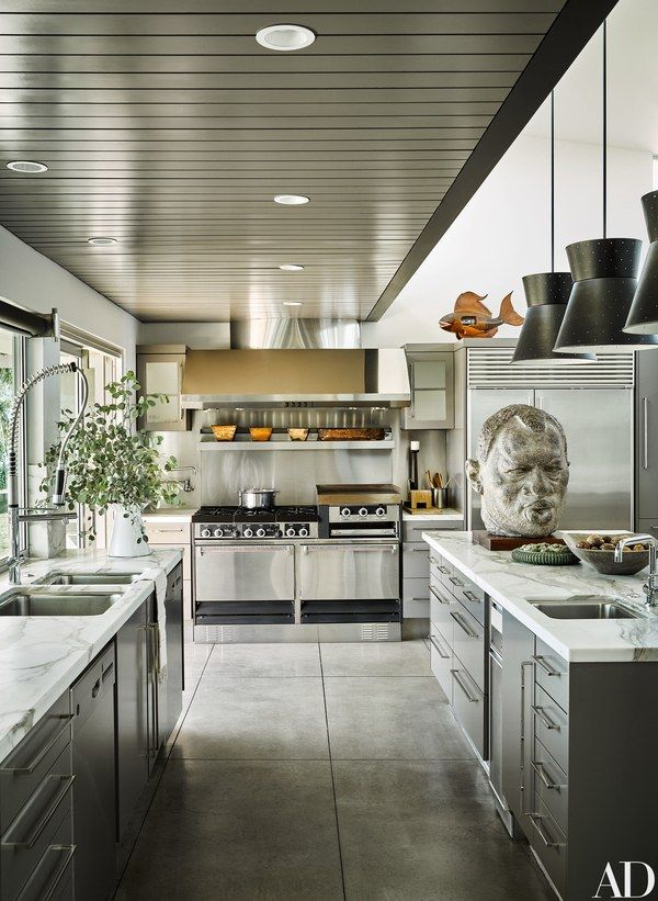 The kitchen boasts a Garland range and hood, Sub-Zero refrigerator, Bosch dishwasher, and Broan trash compactor | archdigest.com