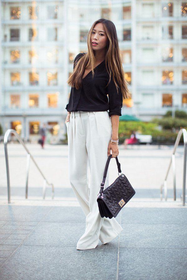 Sehr sophisticated: Die amerikanische Bloggerin Aimee von Song of Style trägt einen schicken, urbanen Street-Style bestehend aus schwarzer Bluse (von Anine Bing) zu einer weiten weißen Hose (von Mango) mit einem schwarzen Täschchen (von Tiffany & Co.). Wie gefällt euch das Outfit?