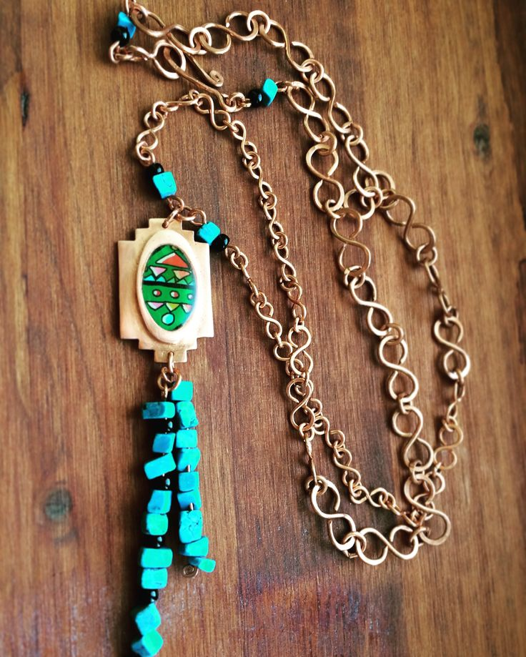 I used copper clay to make the charm, which was fired in my jewelry kiln. The colorful motive is hand drawn by me on paper with posca pencils and coated with a special kind of glue that protects and preserves the colors of the motive. Eventually i cover the motive with resin to finish my charm! For this necklace i also added some turquiose stones and small black pearls.   The chain and hook-and-eye clasp is also handmade from scratch with some of my jewelry tools and pure copper wire.