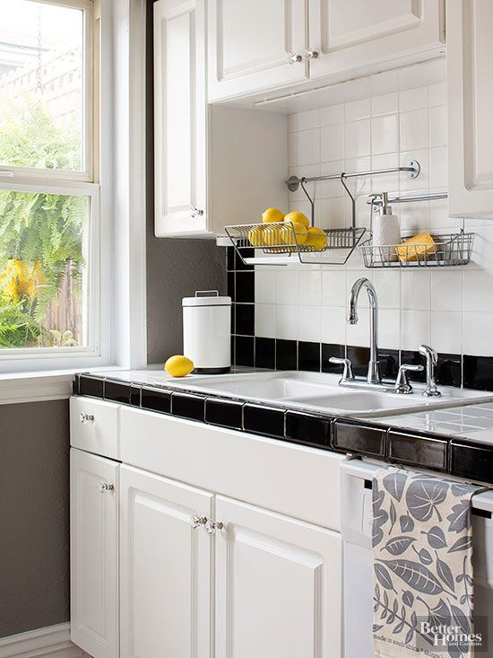 Wire racks above the sink keep kitchen countertops clear. White cabinets and a simple monochromatic backsplash blend seamlessly with the studio's decor. Glass hardware provides the perfect touch of elegance to the fresh but functional area.