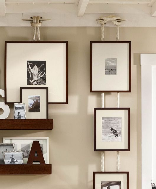 Love this idea from Pottery Barn of hanging pictures from a rope and boat cleat