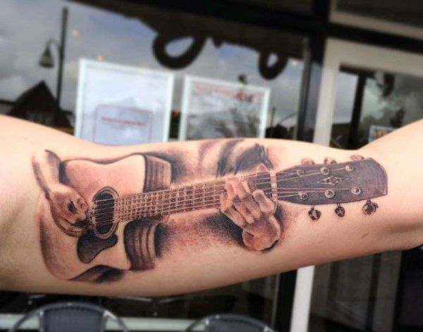 Beautiful and well detailed guitar tattoo on the arm. You can see that the guitar is being played by a pair of hands with a hidden body. The tattoo makes use of the length of the arm to create the guitar body.