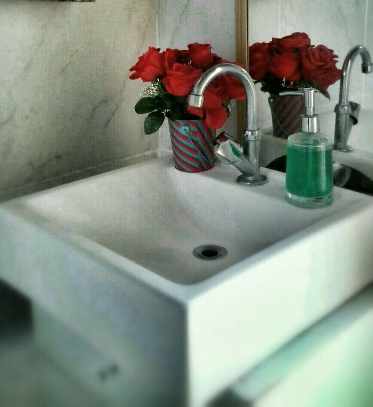 Romantismo e diversão com rosas pink artificial e vaso listrado em lavabo