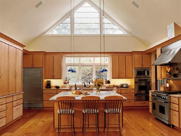in this kitchen a high pitched ceiling transom windows and light