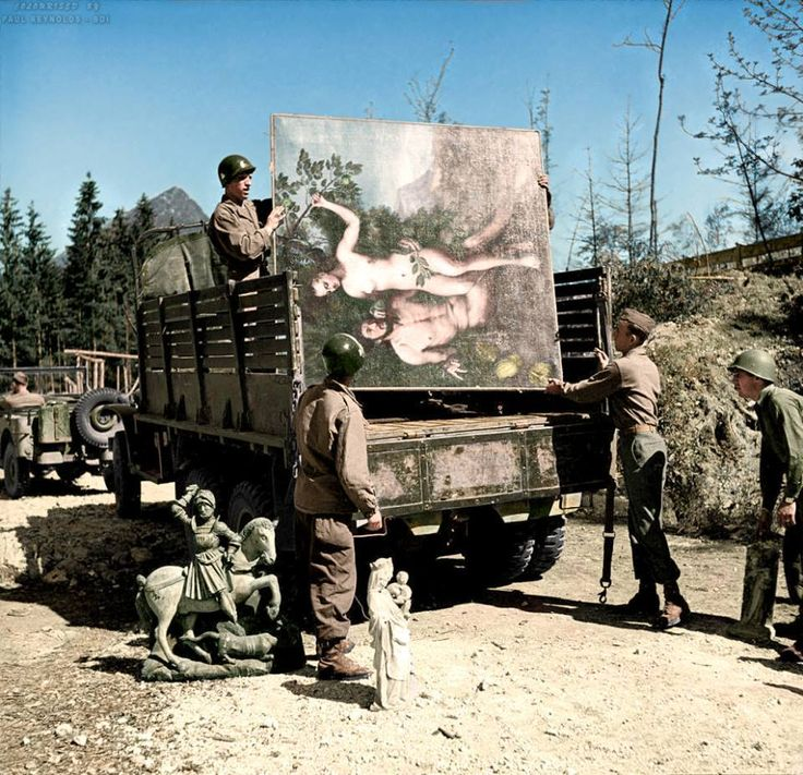 """U.S. soldiers of the 101st Airborne Division carry wooden sculptures and paintings, including the """"Adam and Eve"""" oil painting by Franz Floris from 1550, out of Hermann Goering's art bunker in the Wemholz, Berchtesgaden area, and load them into a truck. May 1945  (Colourisation and Research by Paul Reynolds.)"""