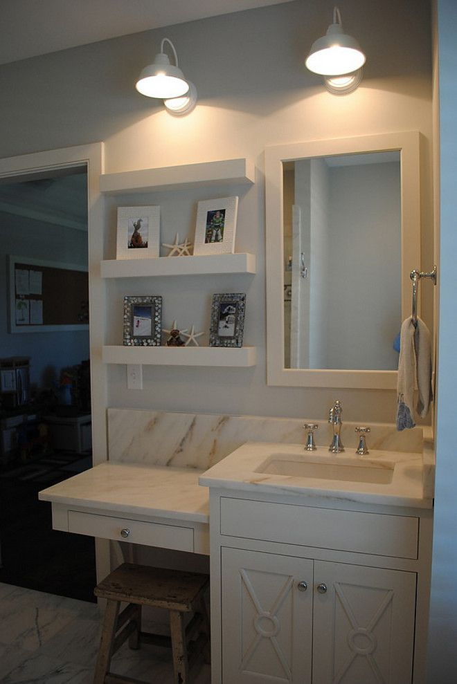 This small bath features custom inset cabinets with Imperial Danby countertops and Barn Light Electric sconces. Stacye Love Construction & Design, LLC.