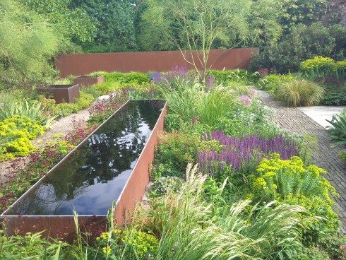 Water feature between drought tolerant plants and grasses