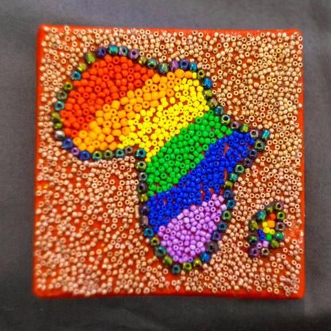 Shop: Canvas D'Afrique - Rainbow. This Africa is partially beaded on canvas in green and yellow with a center of varying blue patterned fabrics. Size: 10cm x 10cm. By Beadoir D'Afrique