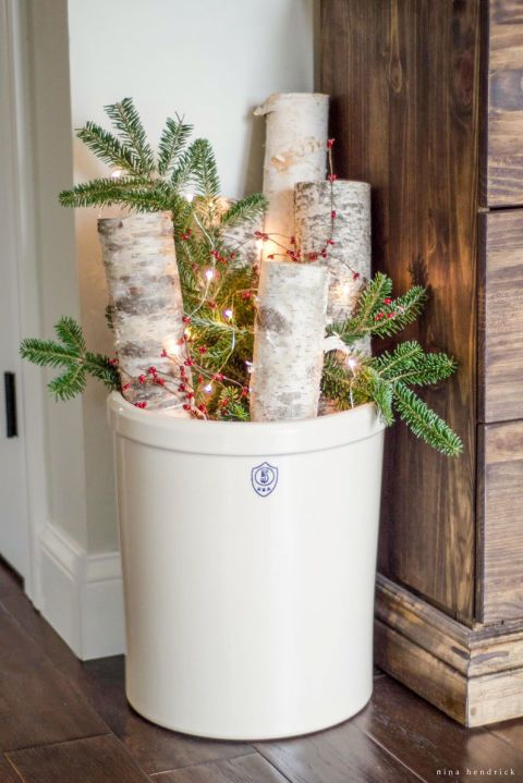 This bundle of birch logs, berries, and Christmas tree clippings will look perfect in the foyer. Add a string of lights for extra sparkle. See more at Nina Hendrick.
