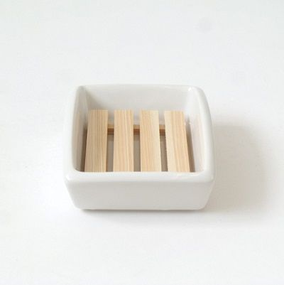 This simple stoneware dish will help preserve the life of your soap in either the bath or kitchen. The wooden rest lets excess water drop into the dish. Unlike plastic or lightweight metal versions, the weight of the dish assures that it stays put. Made in Japan.