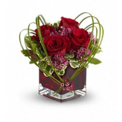 If you'd like someone to think sweet thoughts about you, send them this delightful bouquet! A graceful heart of bear grass is tied with purple waxflower, and appears to float above red roses nestled in a ruby-red glass vase.