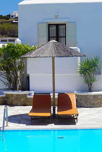 Sunloungers by the swimming pool at the Anastasios Sevasti Hotel in Mykonos. The perfect place for a relaxing Greek Island getaway!