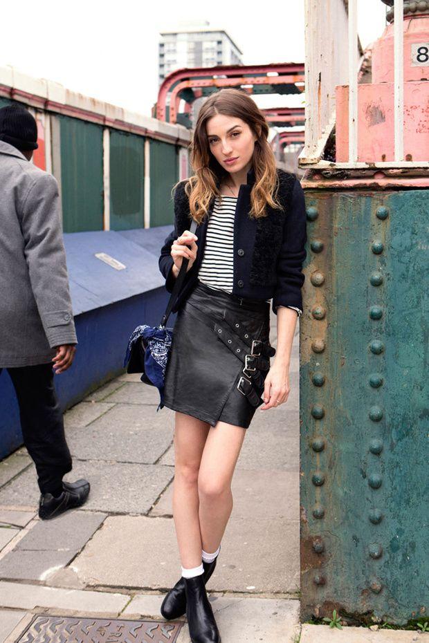 Falda de cuero negra con camiseta de rayas +  botines con calcetines a la vista.