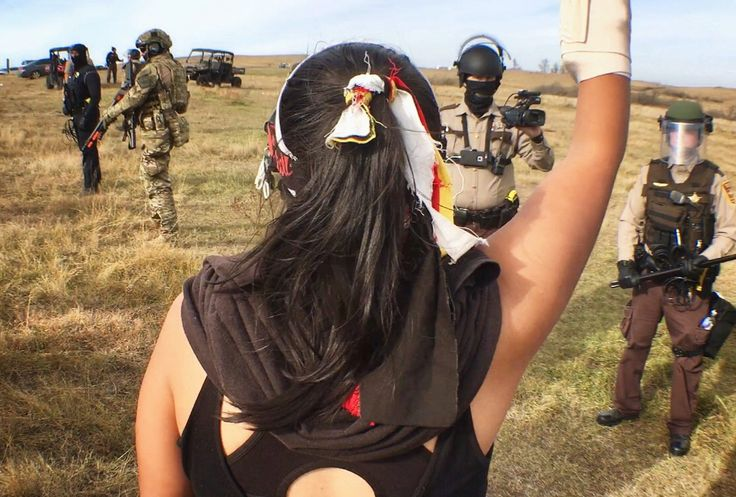 Lauren Howland (Jicarilla Apache), 21, stands before police in resistance to the Dakota Access Pipeline.  Howland is one of thousands who have protested along with the Standing Rock Sioux Tribe to support their fight to protect the Missouri River from pipeline construction. Photo by Jenni Monet for The PBS NewsHour.