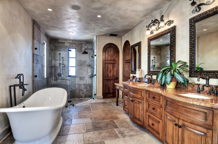 Master Bathroom: Mediterranean, Tuscan, European Architecture, hardware, faucet, pulls, knobs, hardware, European faucets, dual vanities, stained cabinets, raised panel cabinet doors, stone countertop & backsplash, wall sconce lighting, recessed can lights, framed mirror, arch wood windows, arch wood casement windows, stone arch entry shower, stone shower wall & floor, arched stained wood doors, stone floor