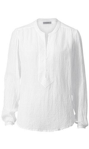 Russel Tunic. Velkendt klassisk hvid bomuldsskjorte fra svenske Hunkydory. Modellen har rund udskæring med stolpelukning, hvor den er prydet med elegant broderi. Lukkes med 3 hægter. Har langt ærme med elatisk og broderi ved håndled. Løs pasform med afrundet bund nederst, og den er lidt længere bagpå. Er lettere transparant.