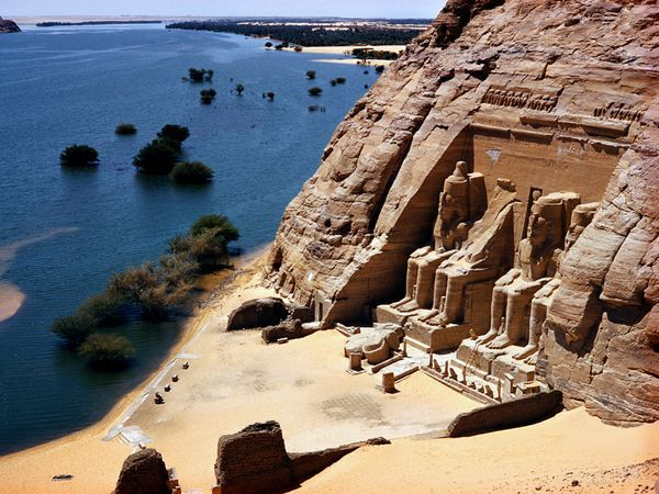 Ramses Temple, Egypt    Photograph by David Boyer, National Geographic    Six-story-high statues rise above the Nile shoreline at Abu Simbel.