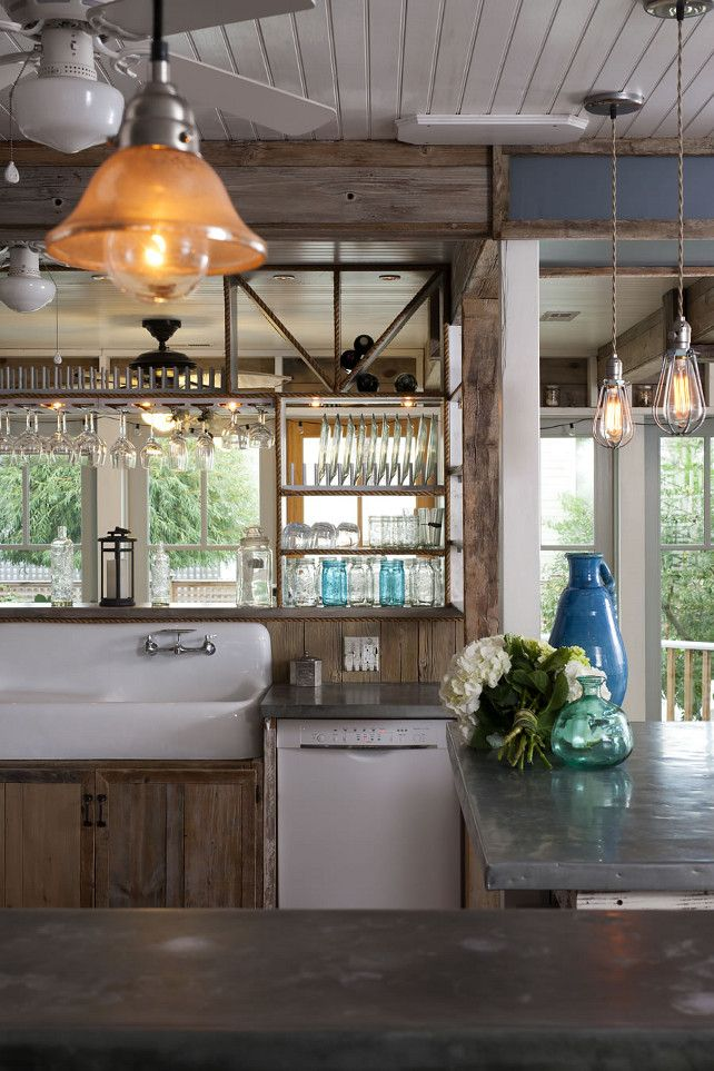 Cottage kitchen with Zinc Countertop, double vintage sink and reclaimed wood cabinets. The open shelves allow the glassware to sparkle in the light.