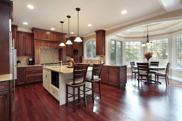 Cherry wood flooring and natural toned wood cabinetry warm up this kitchen, featuring attached dining area and white island.