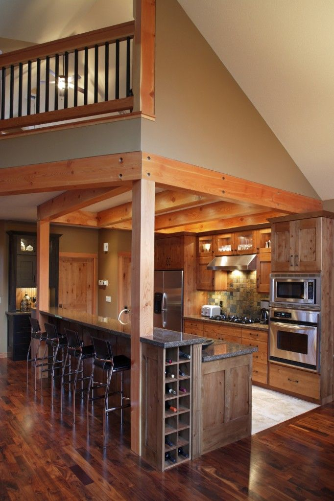 A small kitchen where the majority of the countertop space is centered on the two-tier island. The higher tier is used as a long eat-in bar with room for four. Visible from the side is the built-in wine rack.