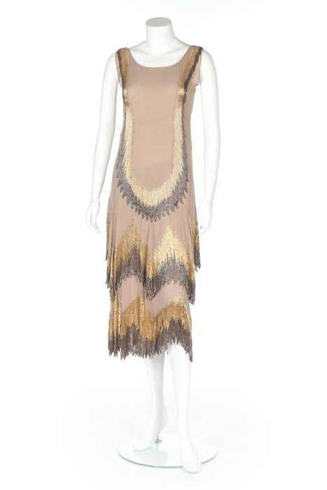 Lot 61 : A Chanel couture beaded beige chiffon flapper dress, 1926-8.  A Chanel couture beaded beige chiffon flapper dress, 1926-8. un-labelled, adorned with pewter-grey and gold bugle beaded zig-zag bands, the skirt falling in two tiers with irregular frond-like edgings, bust 81cm, 32in For an identical model see KTA 10.07.2007, lot 103 which sold for £25,000. For a black chiffon dress altered into a cape with similar beadwork pattern see KTA 26.06.2012, lot 76, which sold for £6,200,.