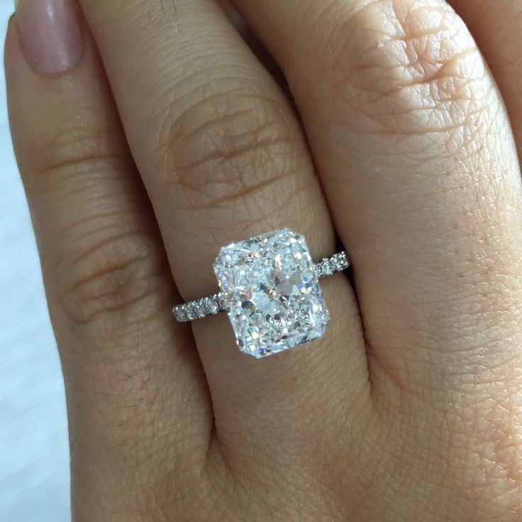 ANNA is a handcrafted Jean Dousset solitaire engagement ring with one row of diamonds on the band and pictured with a Radiant cut diamond in Platinum.