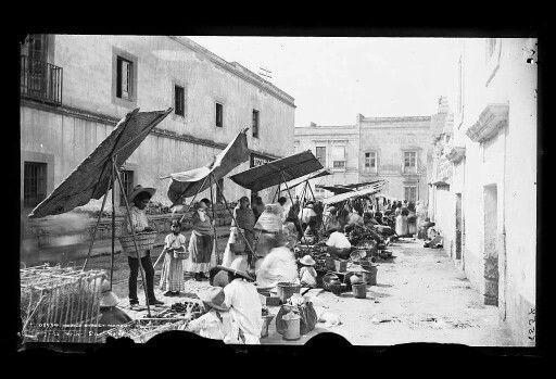 Calle de Academia y Calle República de Guatemala. Una tarde de tianguis. El edificio de la izquierda y los edificios al fondo siguen en pie con sus respecativas modificaciones. Los edificios de la derecha ya no existen.  ca. 1900