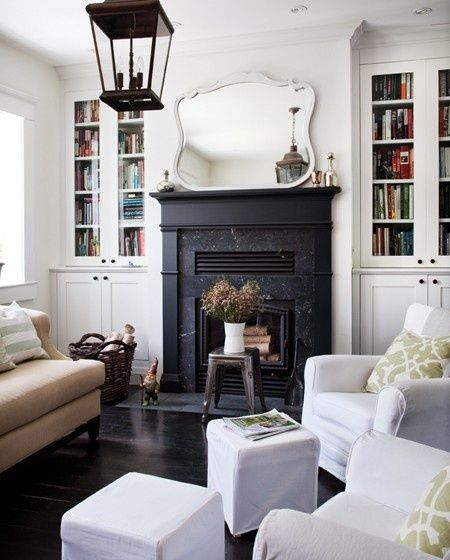 black fireplace, lantern, furniture arrangement, built-in bookshelves with glass doors, mirror above mantel