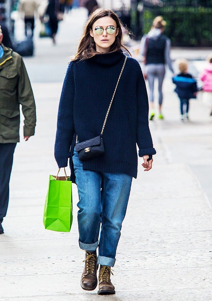 Keira Knightley wears a navy blue sweater, cuffed jeans, a Chanel bag, Dr. Martens boots, and round sunglasses