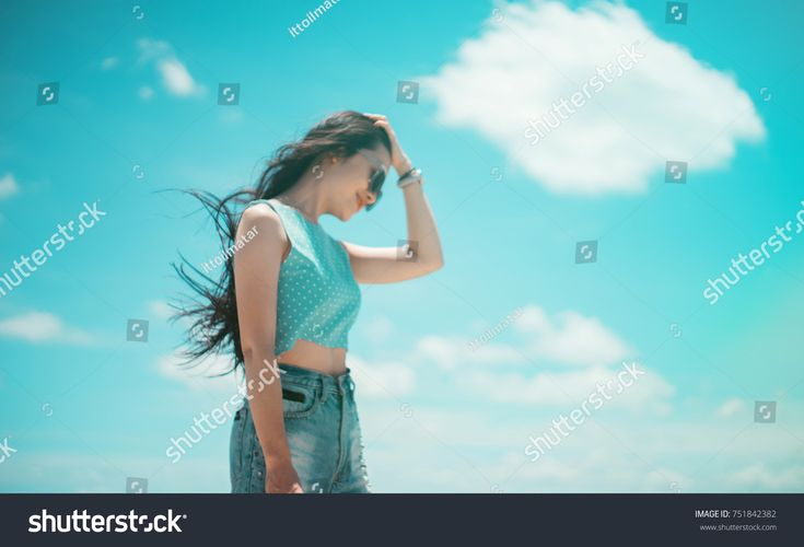 portrait of cute asian woman wearing a sunglasses and wind blow her hair. teenager travel in summer season concept. hipster tone color filtered image. Intentionally blurred editing post production