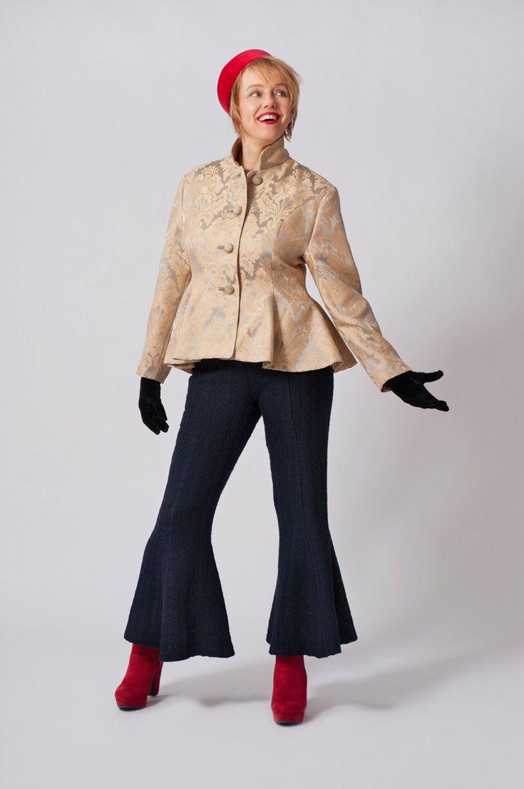 Geel gobelin klokkend jasje. Blauwe wollen broek met uitlopende pijpen vanaf de knie.