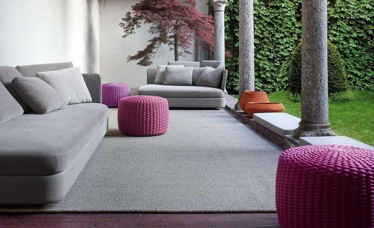 Graues Outdoor-Sofa und lila handgewebter Hocker auf der Terrasse