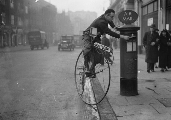 Tornado Smith posts a letter while riding penny farthing bicycle.