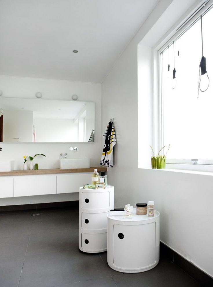 Badeværelset er indbydende med masser af lys gennem det matterede vindue med de spøjse wallstickers 'Light Bulb' fra Ferm Living. Gulvfliserne er fra Flisegalleriet, de hvide toiletborde fra Kartell, mens vasken er fra Villeroy...