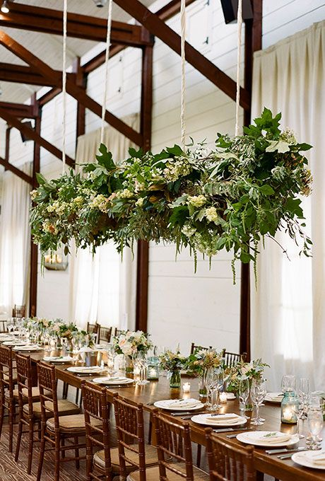 A statement-making floral chandelier packed with tons of greenery, pink and peach roses, and white hydrangea | Brides.com
