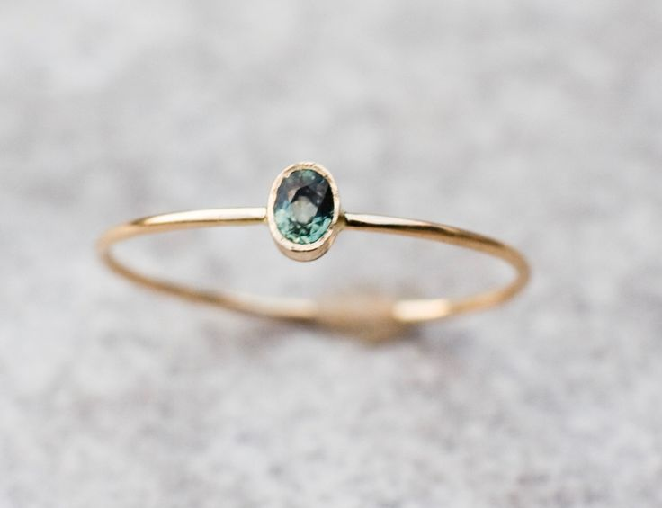 Tiny green sapphire ring in 14k yellow gold.   The sapphire in this ring is  natural gemstone- Earth mined, not synthetic or lab created.   The stone and the stone setting measures: 4.7mm X 3.6mm   The shank measures 0.9mm  This ring is handcrafted by Me in my studio.  In the back  I ca...